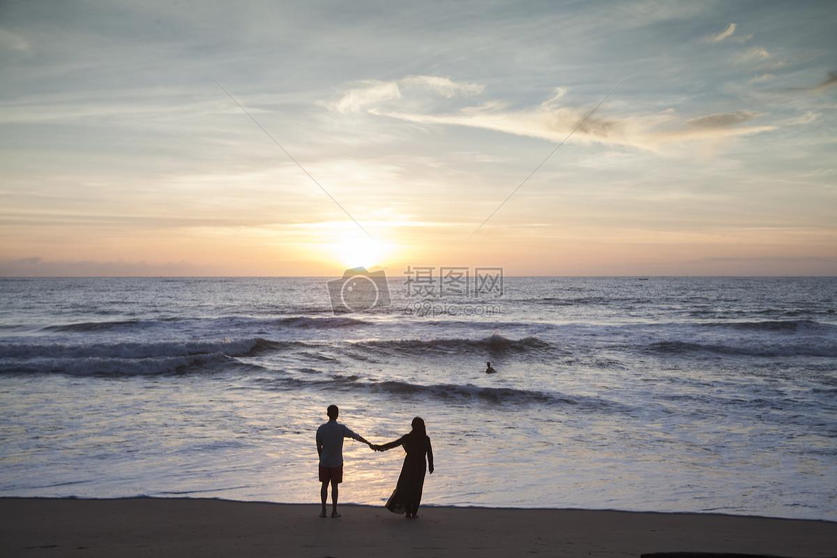情侣在夕阳西下的海边看大海