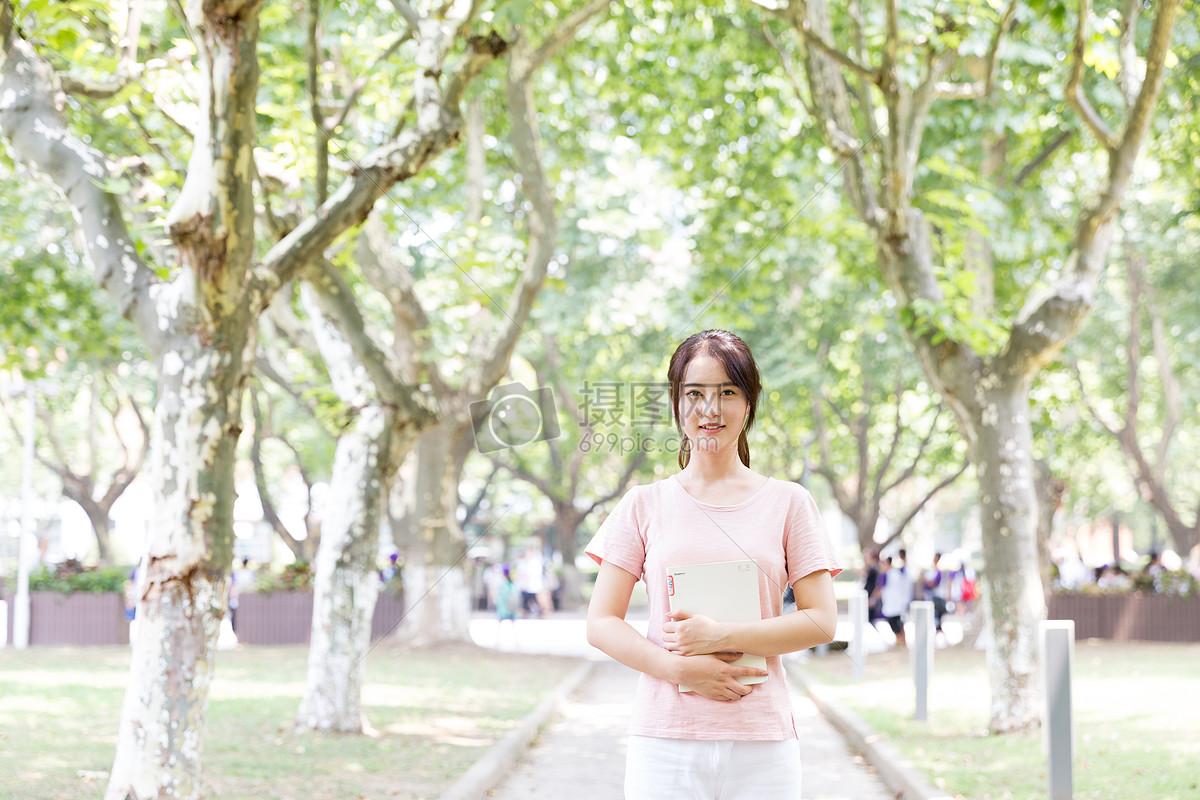 拿著書站在校園林蔭道上的女生