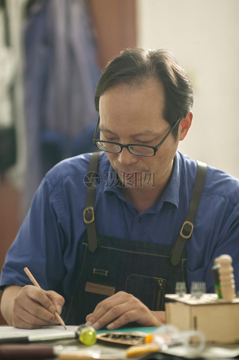 皮匠师傅在专注画皮具草稿图片