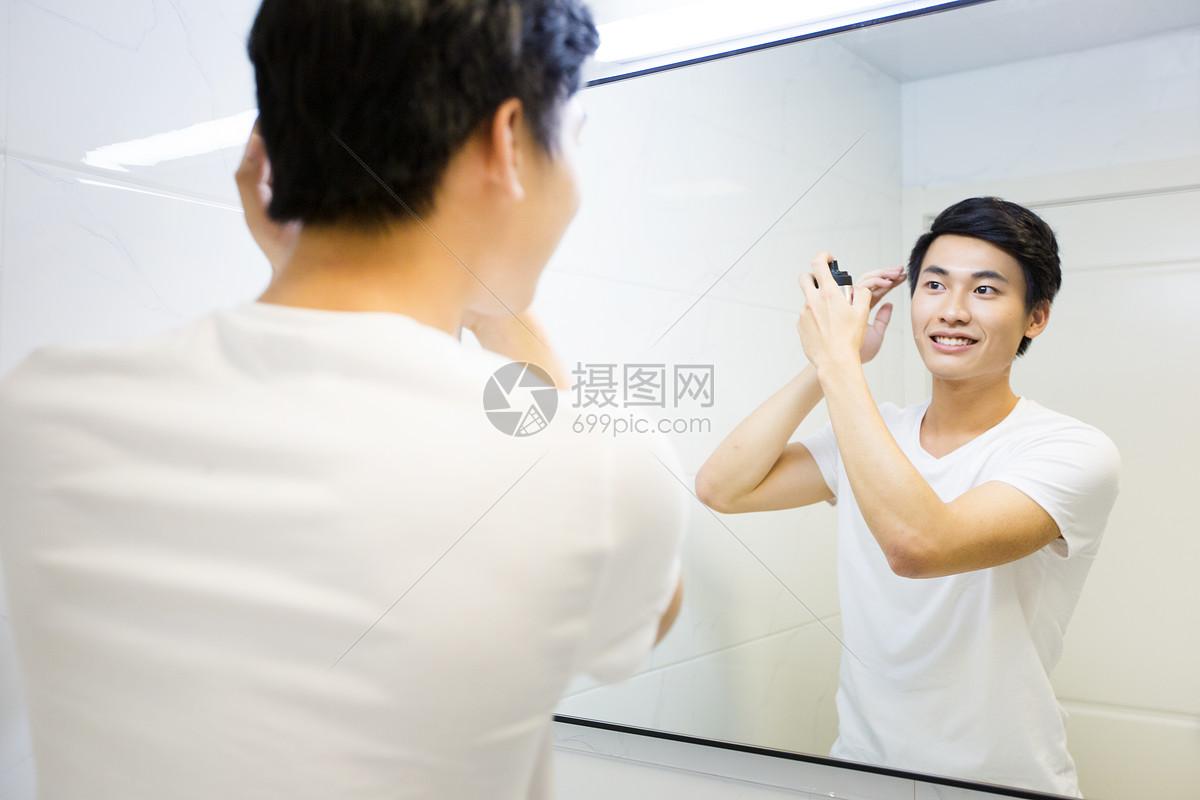 年轻男子在浴室整理头发图片