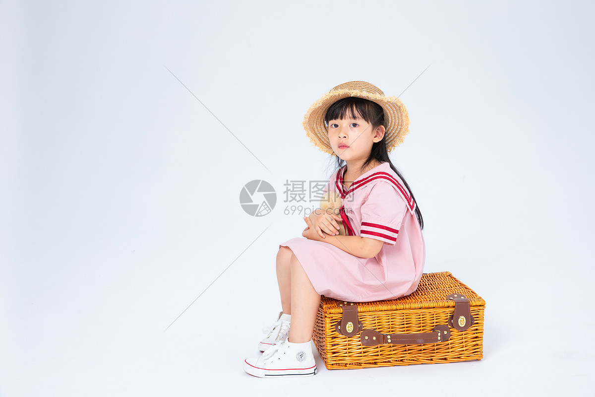 坐在旅行箱上的小女孩