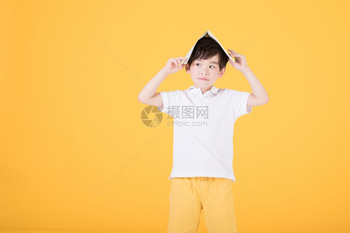 小男孩手持书本学习儿童教育图片