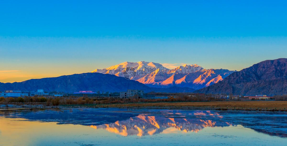 落日照雪山倒影图片