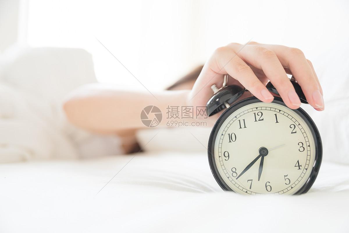 年轻女性起床困难按闹钟特写图片