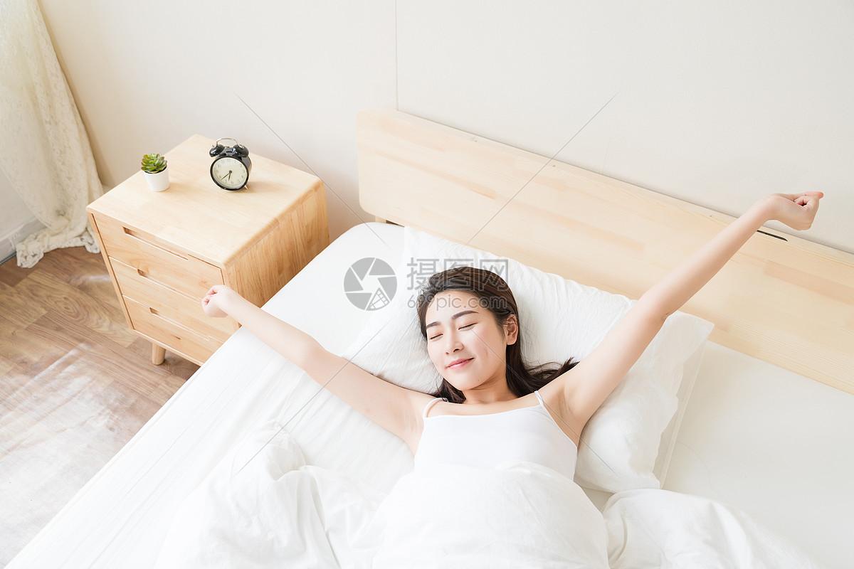 年轻美女床上伸懒腰图片