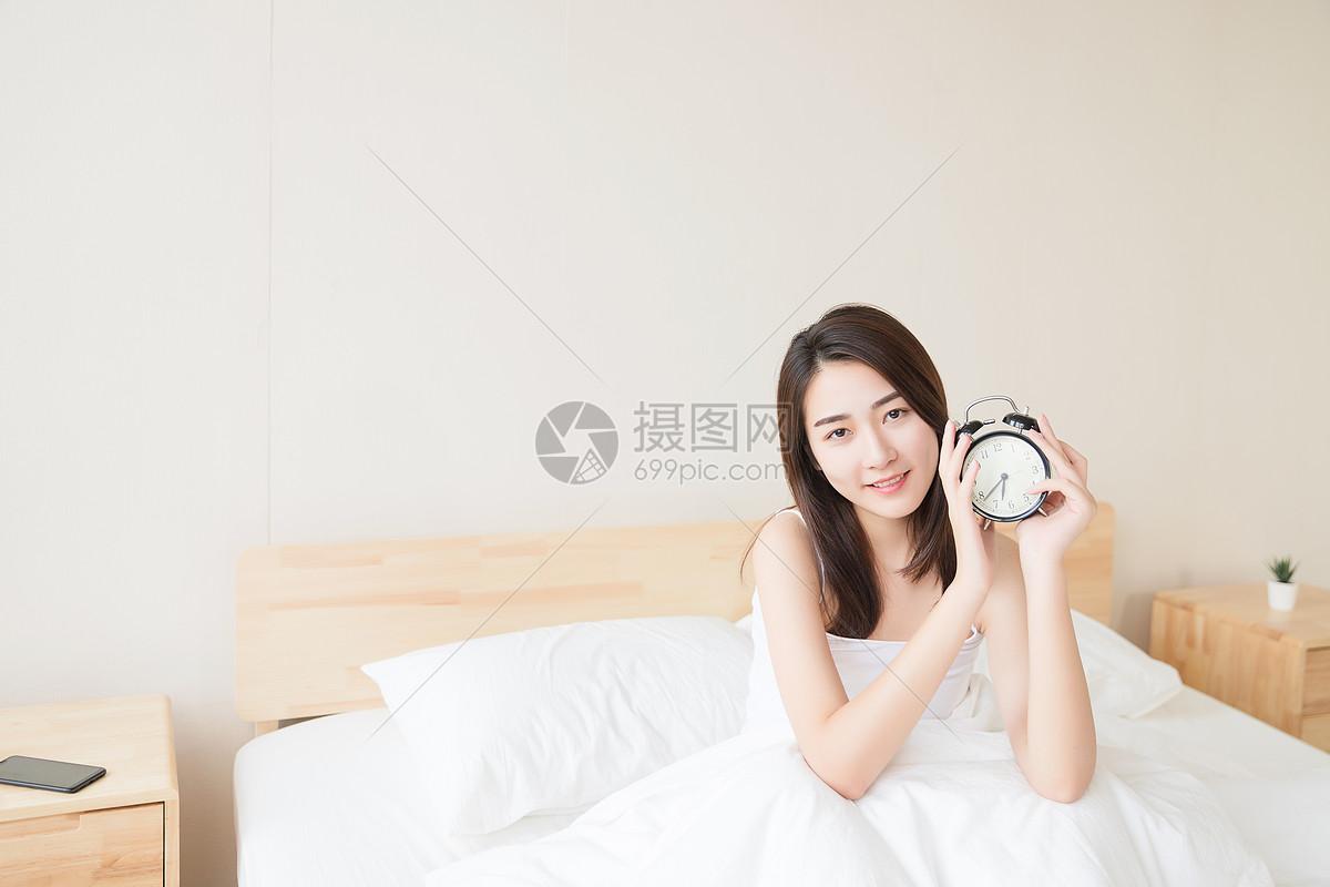 年轻女性起床与闹钟图片