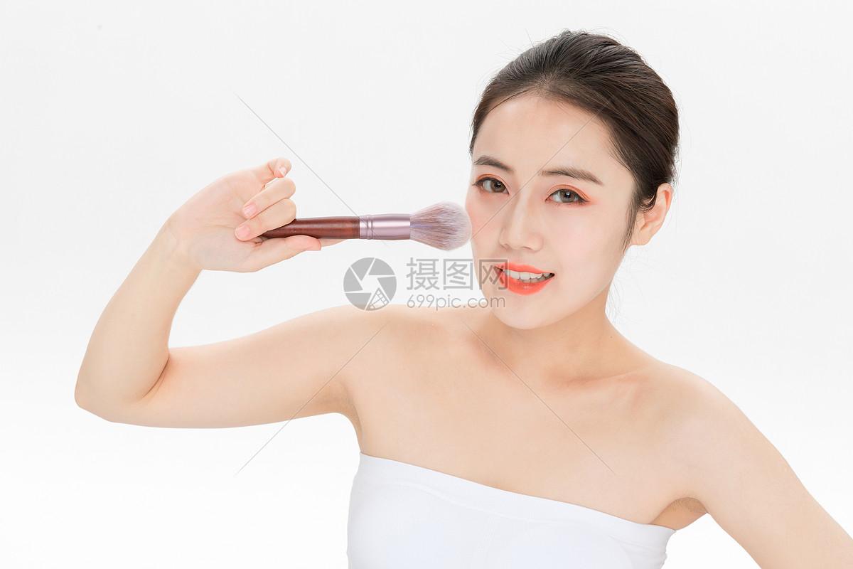 女性化妆拿粉底刷图片