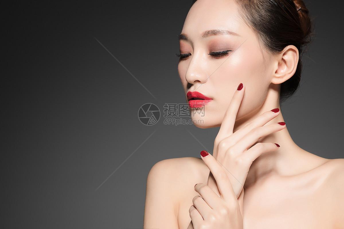 女性美妆与红色美甲图片