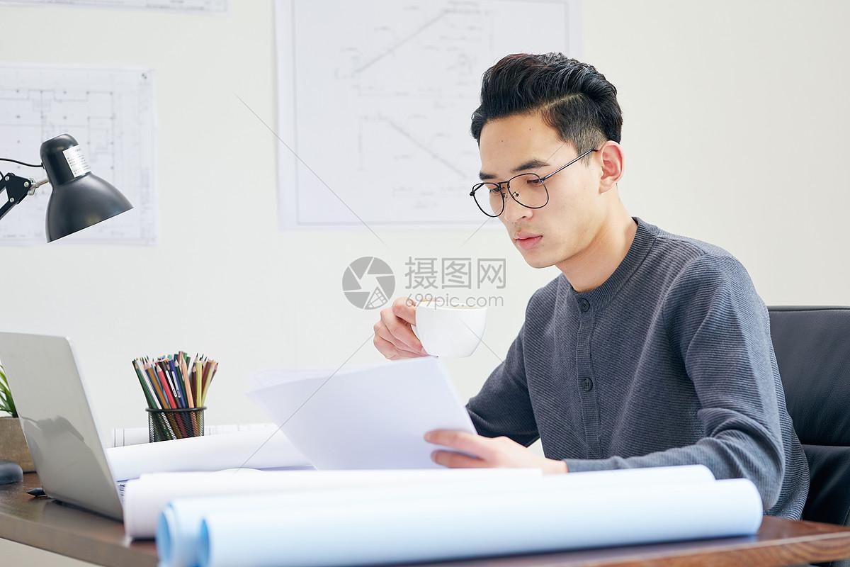 年轻男设计师查看图纸图片