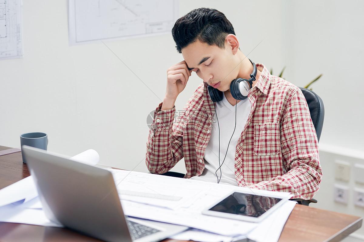 年轻男设计师工作劳累图片