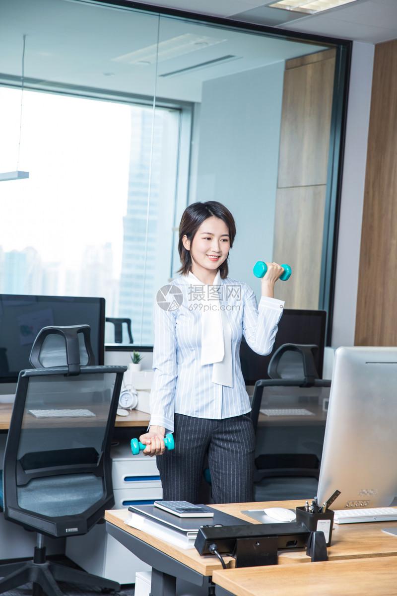 女性工作办公室锻炼哑铃图片