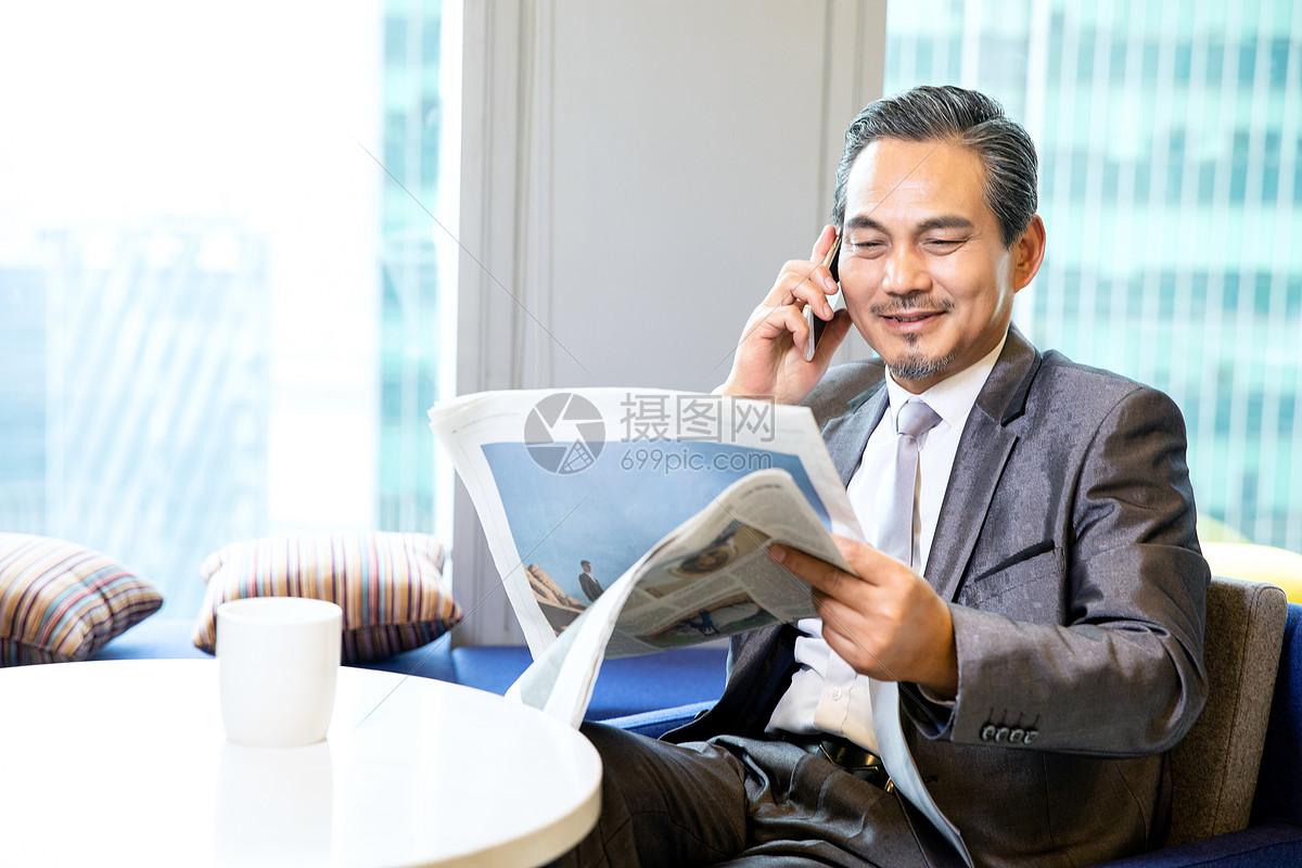 商务男性看报纸打电话图片
