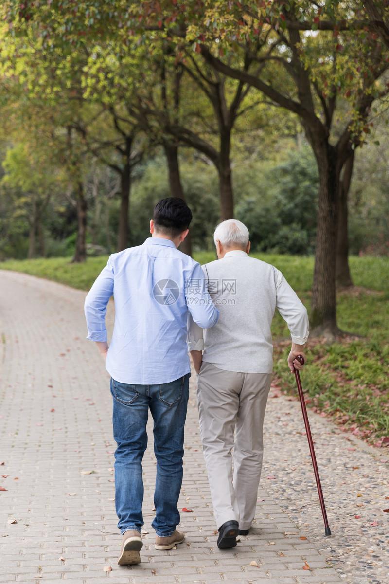 老年父子陪伴散步背影图片