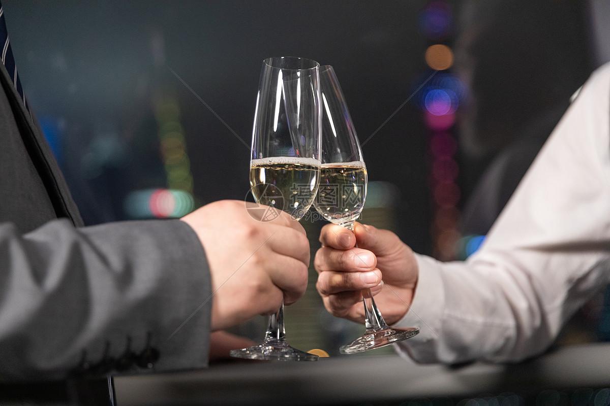 商务男性手持香槟碰杯图片
