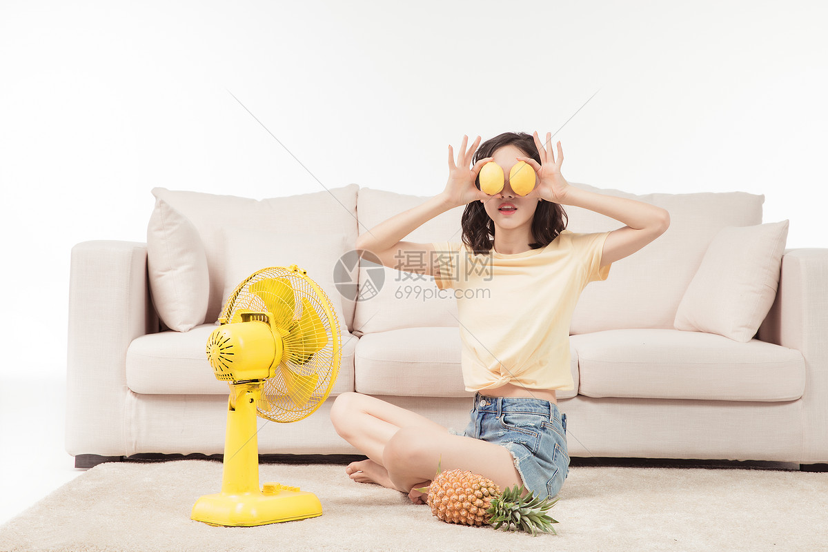 青年女子在客厅吹风扇图片