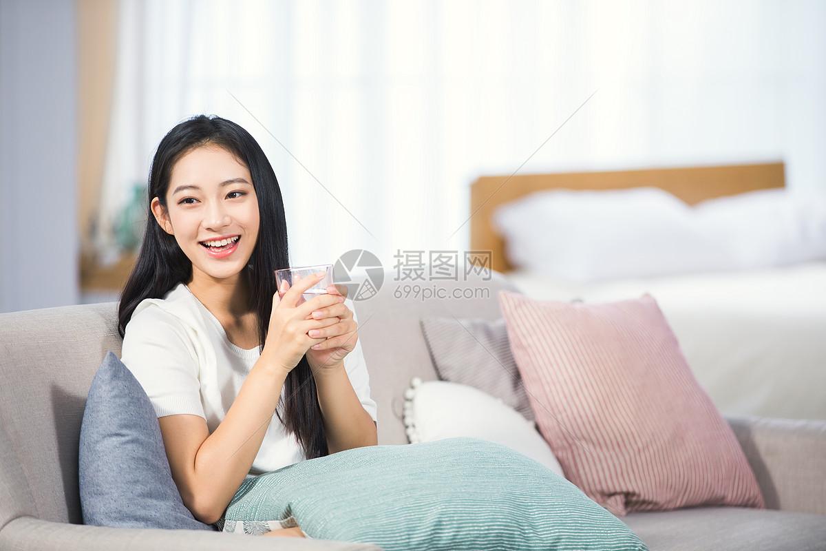 女性坐在沙发上喝水图片