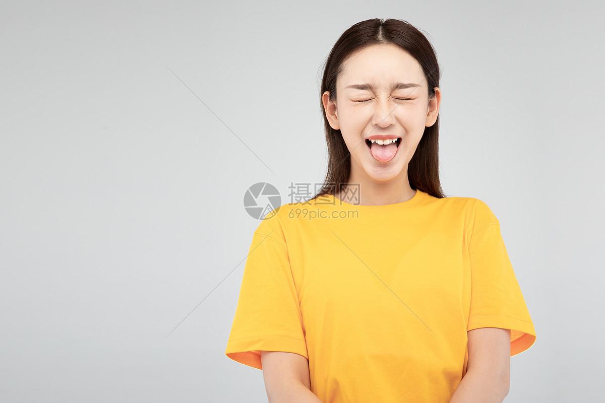 青年可爱女性吐舌头图片