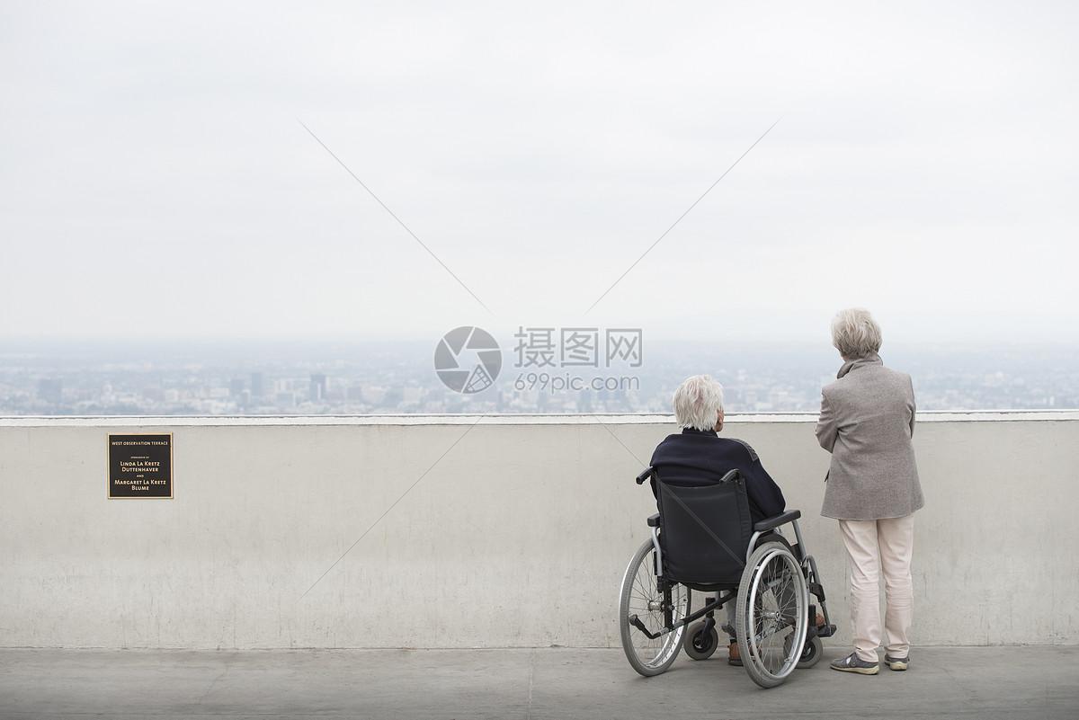美国加利福尼亚州洛杉矶格里菲斯公园天文台观景台上坐轮椅的老人和他的妻子观看城市的后视图图片