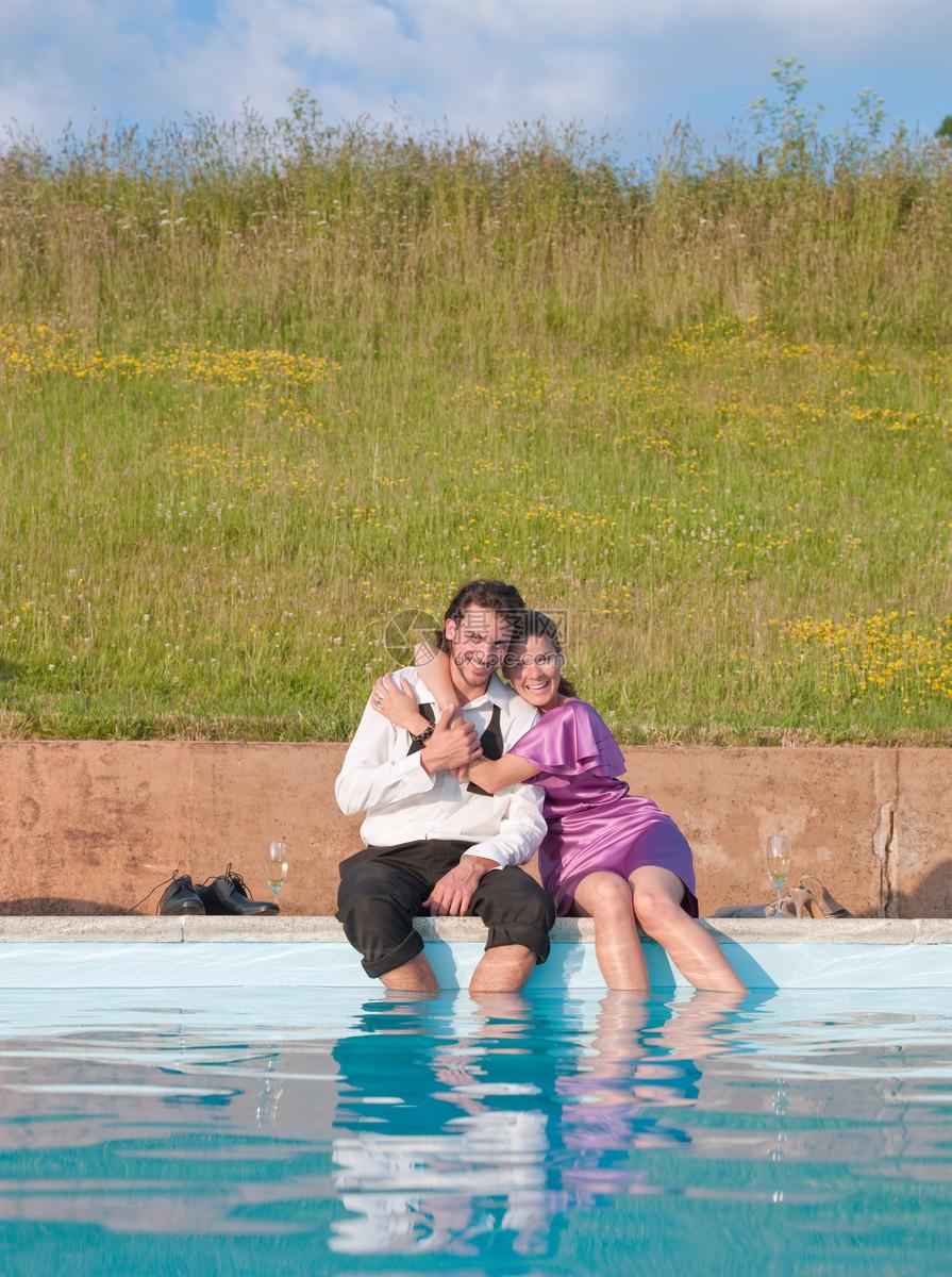 青年夫妇坐在游泳池旁拥抱图片