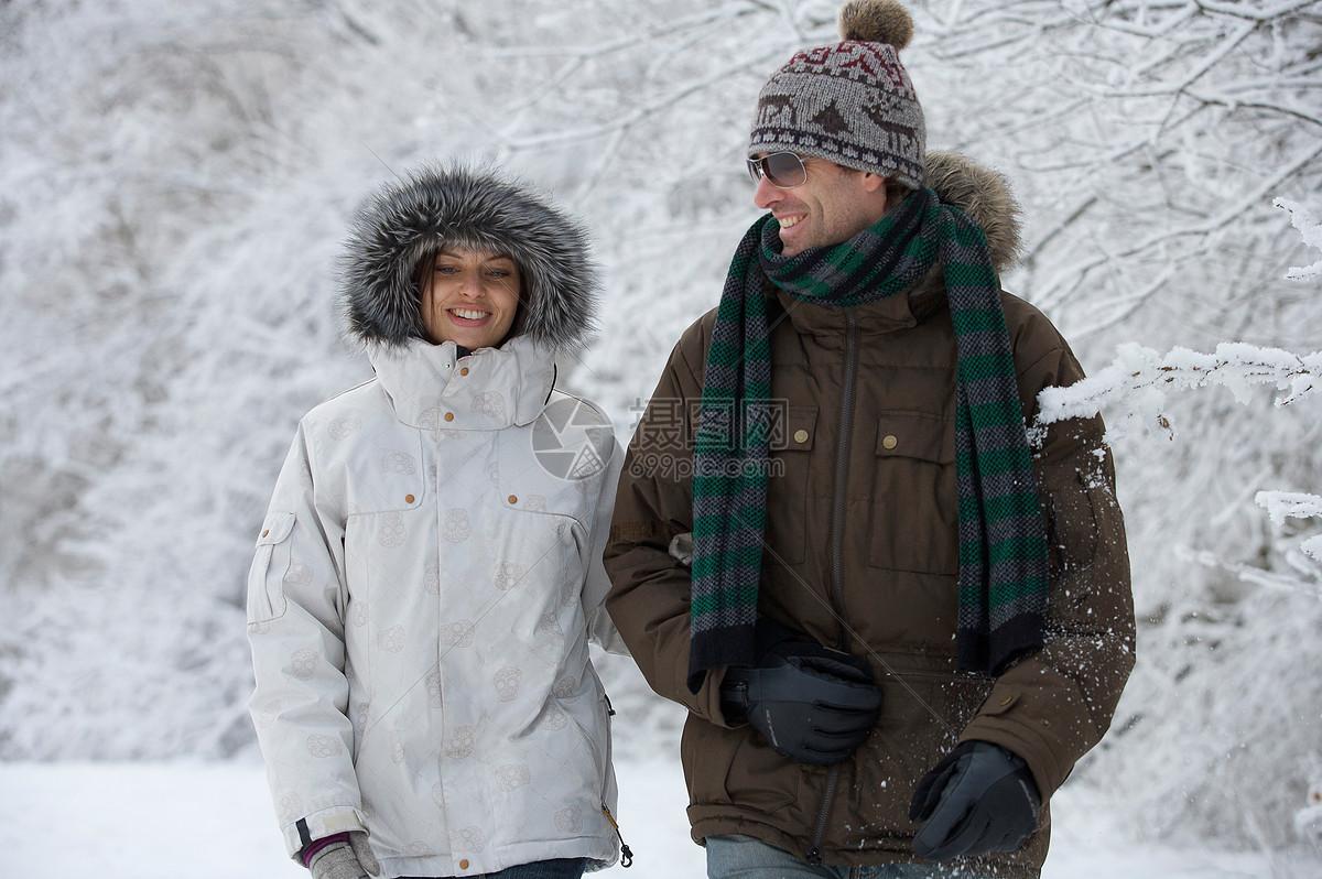 一对在雪中行走的夫妇图片