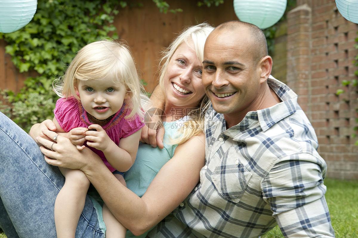 一对幸福的夫妇和幼小的女儿坐在花园里的照片图片