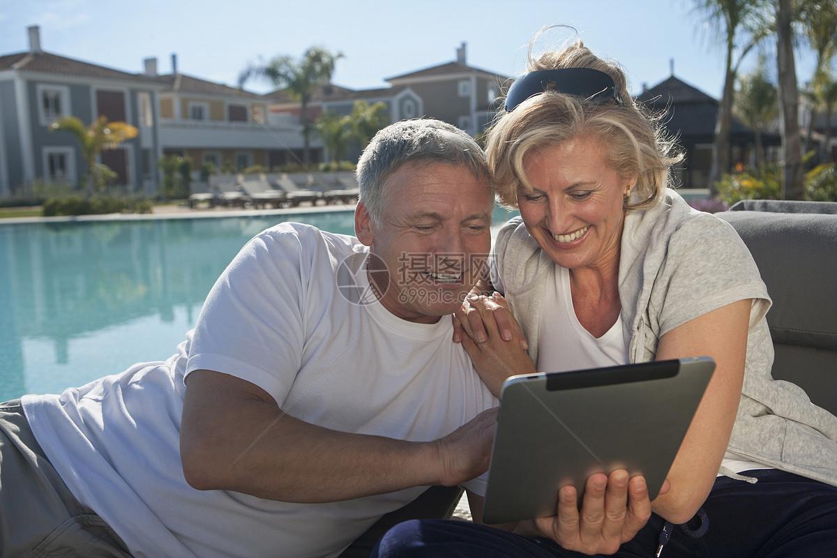 一对夫妇在泳池边使用平板电脑图片